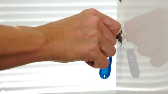 Female Hand Using Key with Blue Keyholder To Open Metal Door in White Shelf. Hand Opens Steel Cell
