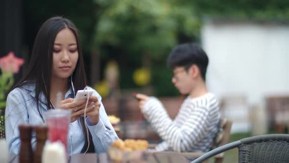 Thumbnail for Asian Woman Listening to Music and Texting on Phone at Cafe Table