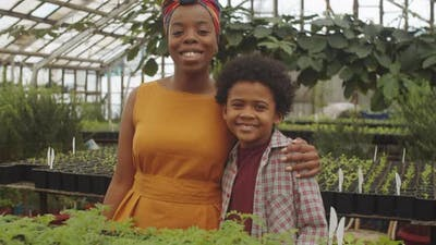Portrait of Joyous Afro-American Mother and Son in Greenhouse
