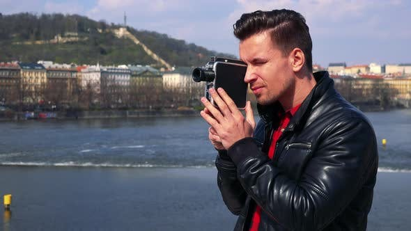Thumbnail for A Young Handsome Man Shoots a Video with a Camera - Closeup - a River and a Quaint Townscape