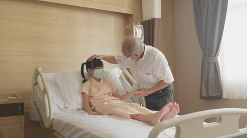 Asian young little girl kid wearing mask lying on bed in recovery room and father comes to visit.