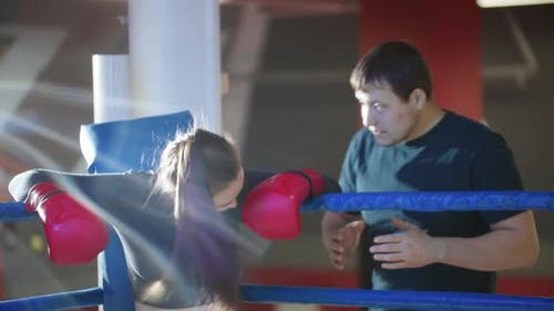 An Attractive Young Woman with Long Hair Resting on the Boxing Ring and Her Trainer Talks To Her