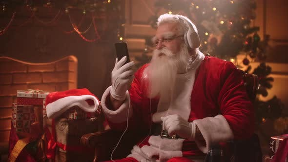 Thumbnail for Merry Santa Claus Is Viewing Video on Smartphone and Listening To Music By Headphones in Decorated