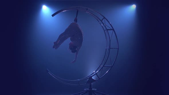 Thumbnail for Gymnast in a Brilliant Costume Performs Tricks on a Special Design Moon . Blue Smoke Background