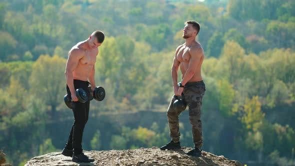 Thumbnail for Shirtless sportsmen lifting weights outdoors
