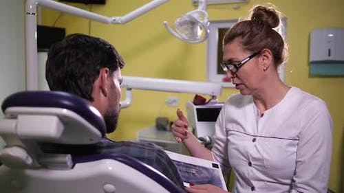 Woman Dentist Showing Patient X-ray Scan of Jaw