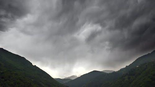 Dicke dunkle Stratonimbuswolken bedeckten das Tal zwischen bewaldeten Bergen