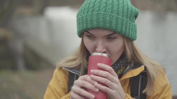 Cover Image for Portrait of Pretty Woman in Green Hat and Yellow Coat Drinking Tea or Coffee From the Thermos