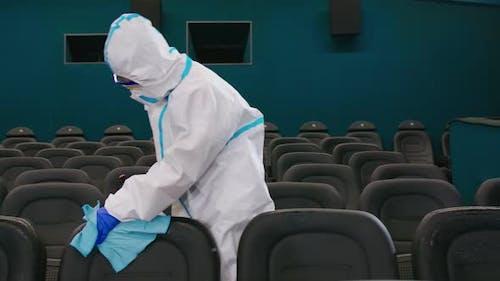 Man in Antivirus Uniform Spraying Disinfectant at Cinema