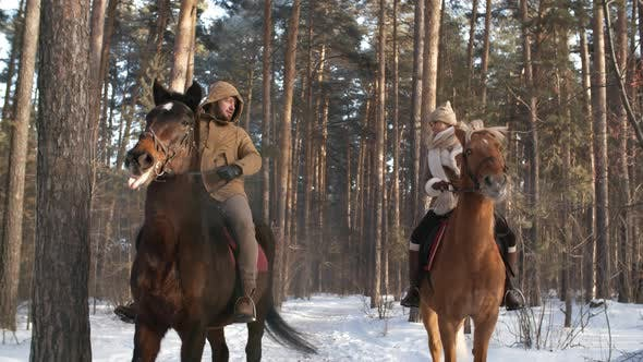 Cover Image for Happy Couple Riding Horses in Winter Park