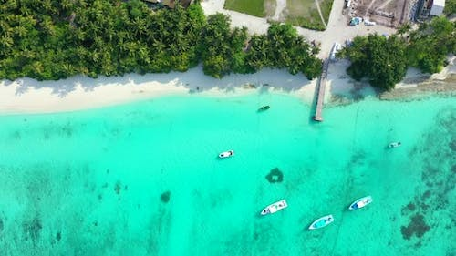 Daytime overhead travel shot of a paradise sunny white sand beach and aqua turquoise water backgroun