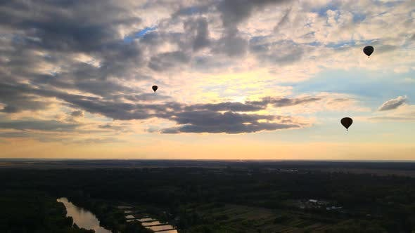 Thumbnail for Silhouettes of Hot Air Balloons Flying Over Countryside Near Small European City at Summer Sunset in