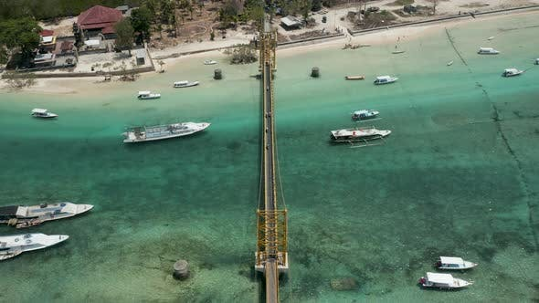 Cover Image for Aerial view of a small suspension bridge connecting two tropical islands