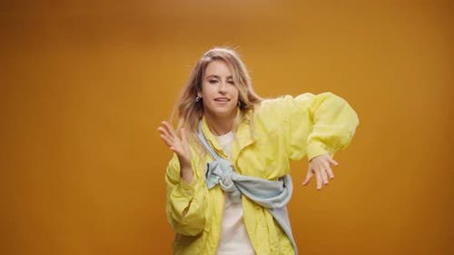 Woman Professional Dancer Dancing in Studio Against Yellow Background