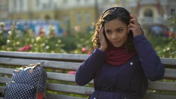 Cover Image for Girl Putting on Earphones, Enjoying Atmosphere of Favorite Band Concert