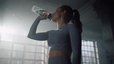 Sportswoman Drinking Water in Gym