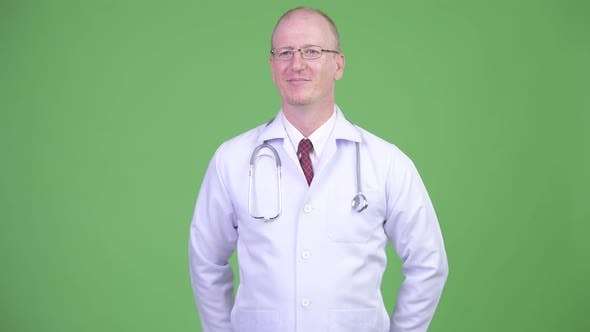 Thumbnail for Happy Mature Bald Man Doctor Greeting Someone Against Green Background