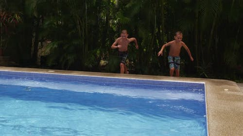 Two boys jump into swimming pool. slow motion Shot on RED EPIC for HQ 4K UHD Ultra HD resolution