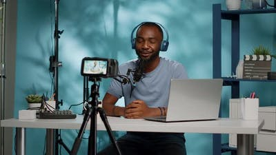 Vlogger Recording Video on Camera with Tripod in Studio