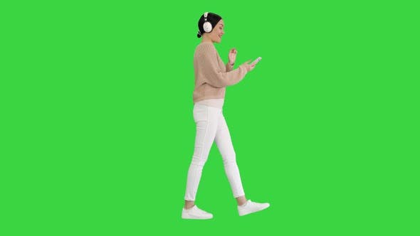 Happy Girl Walking Listening To Music with Smart Phone Wearing Headphones on a Green Screen, Chroma