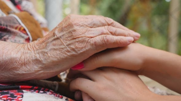 Thumbnail for Old wrinkled and young female hands comforting and stroking each other. Caring and loving concept