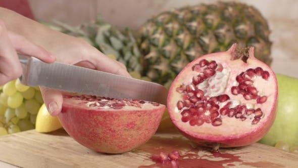 Cover Image for Cuts a Juicy Fruit of Pomegranate