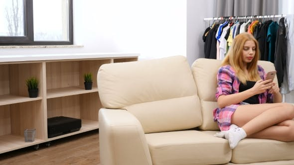 Thumbnail for Woman Sitting on the Couch in Her House Using a Smartphone