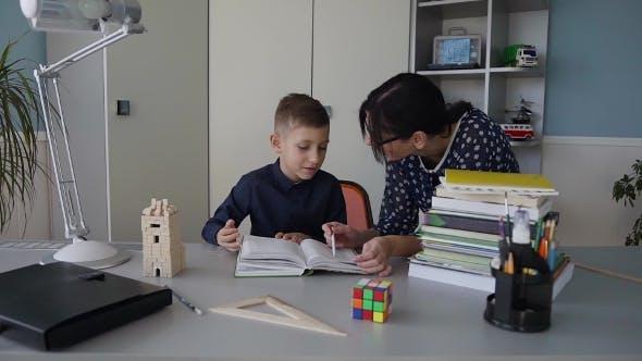 Thumbnail for Ein junger Lehrer lehrt eine Grundschule Schüler zu lesen Buch gut Hausaufgaben erklären Hausaufgaben