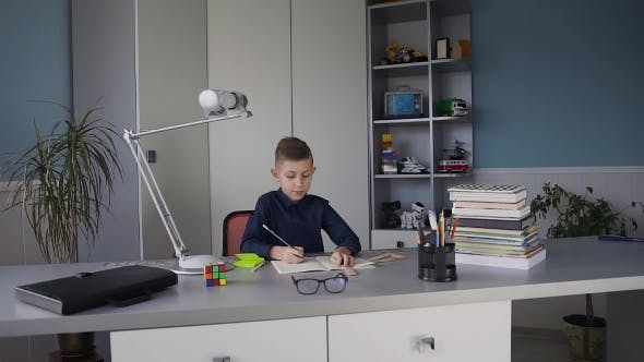 Thumbnail for Young Cute Boy in a Blue Shirt Sitting at a Desk in His Room and Doing a Homework Books on the