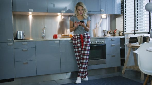 Thumbnail for Young Woman Browsing Smartphone in Kitchen