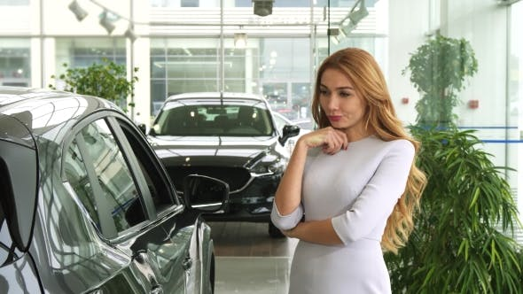 Thumbnail for Female Customer Looking at the New Car Thoughtfully Choosing Auto at the Dealership