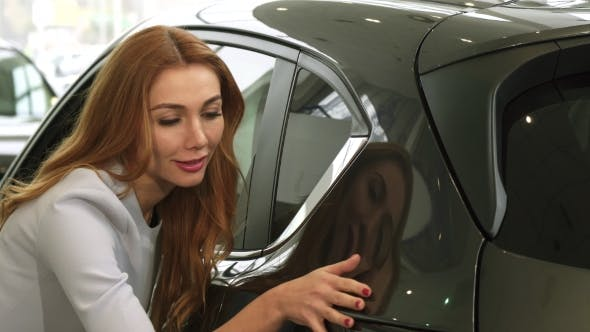 Thumbnail for of a Gorgeous Woman Examining a New Car at the Dealership