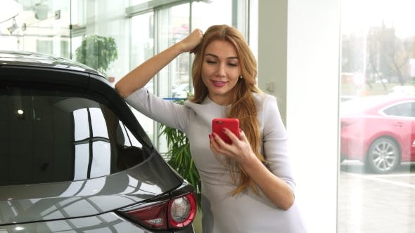Thumbnail for Happy Beautiful Woman Using Her Smart Phone at the Car Dealership Salon