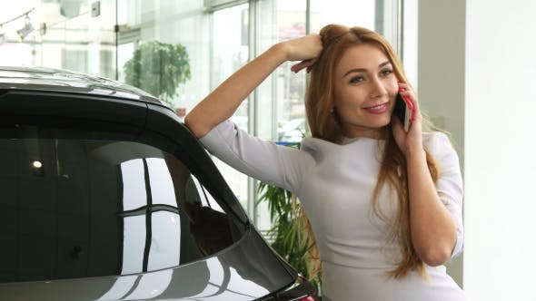 Thumbnail for Gorgeous Woman Talking on the Phone at the Car Dealership Showroom
