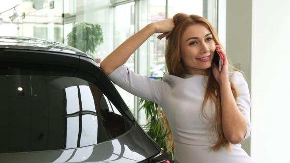 Thumbnail for Wunderschöne Frau im Gespräch am Telefon im Autohändler Showroom
