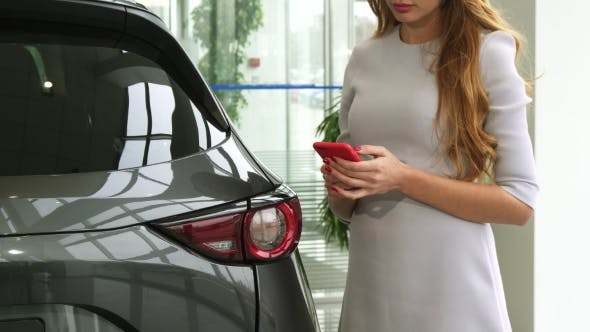 Thumbnail for Cropped Shot of a Woman Using Smart Phone at the Car Dealership