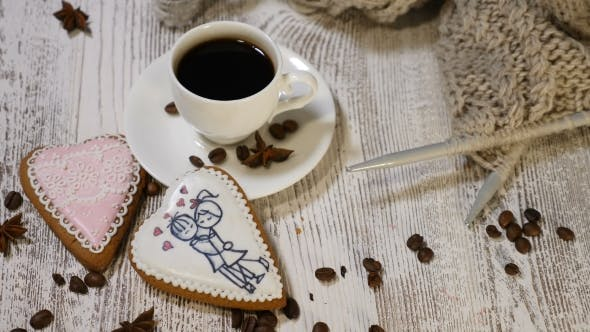 Couple Relations St Valentine`s Day Concept A Cup of Coffee and Ginger Biscuit with Knitting