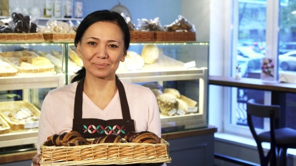 Mature Female Baker Posing at Her Store with a Basket Full of Croissants