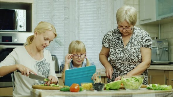 Cover Image for For Three Generations, the Family Together Prepare a Salad in the Kitchen. Grandma, Mom and