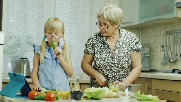 Thumbnail for Funny Girl 6 Years Old Helps Her Grandmother Prepare Meals in the Kitchen. Eats a Cucumber, Have Fun
