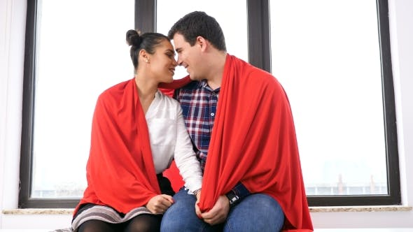 Thumbnail for Romantic Couple Covered with a Blanket Next To a Big Window