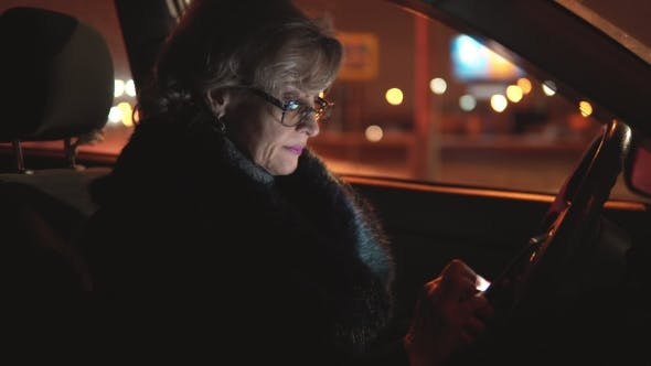 Thumbnail for Attractive Middle-aged Woman Use the Phone in the Car