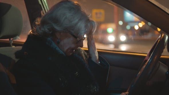Cover Image for Tired Middle-aged Woman Is Sitting in the Car While Driving
