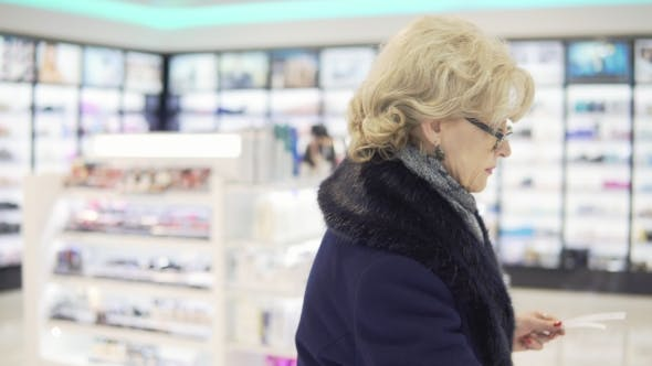 Thumbnail for A Middle-aged Woman Is Choosing Perfume in a Store