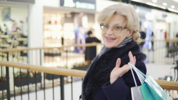 Thumbnail for An Attractive Middle-aged Woman Strolls Through the Shopping Center with Purchases