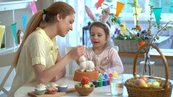 Mother and Her Little Daughter with Bunny Ears Painting Easter Bunny