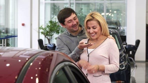 Thumbnail for Liebevoller Ehemann präsentiert seine Frau ein neues Auto bei der Händlerschaft