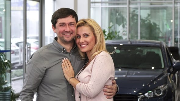 Thumbnail for Happy Couple Laughing High Fiving After Buying a New Car at the Dealership