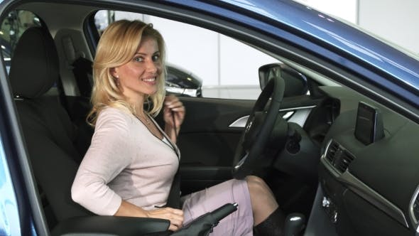 Thumbnail for Reife Frau Befestigung Sicherheitsgurt sitzt in einem neuen Auto bei der Autohaus