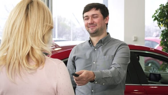 Thumbnail for Happy Mature Man Handing Car Keys To a New Auto To His Loving Wife